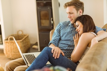Happy young couple relaxing on the couch with laptop