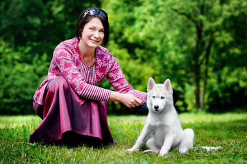 Smiling young woman with a puppy husky