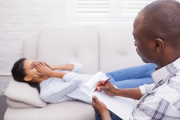 Therapist writing notes on his crying patient on the couch