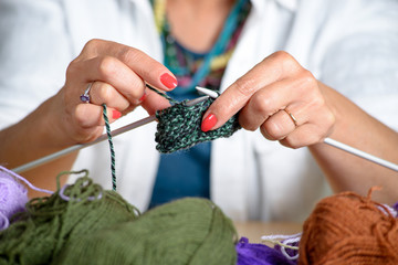 close up of the hands of a woman who knits