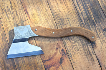 Old axe over wooden background