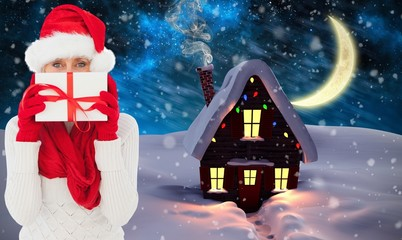 Composite image of festive woman holding gift