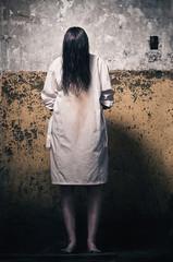 Horror scene with girl in a white coat