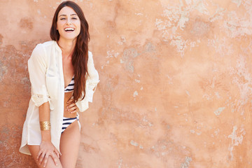 Pretty Young Woman Wearing Swimsuit Leaning Against Wall