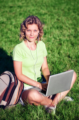 Beautiful girl sit with laptop listening music on green grass