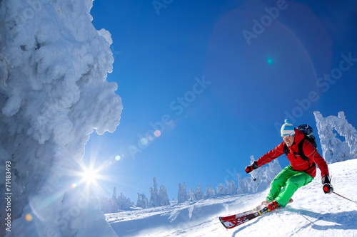 canvas print picture Skier against blue sky in high mountains