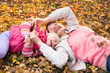 mother and kid have fun laying on autumnal leaves outdoors