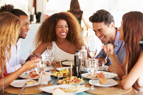 Group Of Young Friends Enjoying Meal In Outdoor Restaurant - 71483893