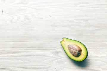 halved avocados on wooden background
