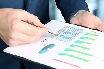 Businessman standing and showing graphics, diagram. Presentation