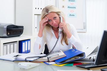 überforderte geschäftsfrau am telefon