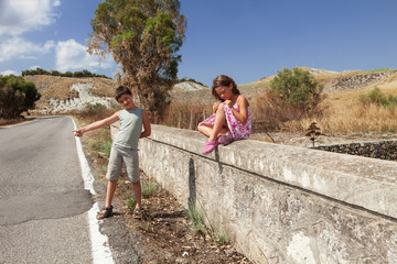 young boy hitchhiking with her sister
