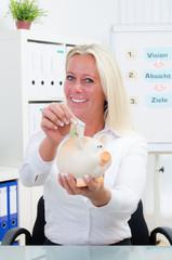 businessfrau wirft geldschein ins sparschwein