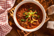 overhead photo of a bowl of chili with cheese and green onions - 71486010