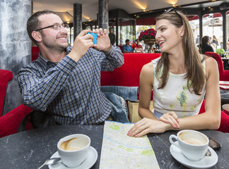 Couple Taking Photos in a Cafe