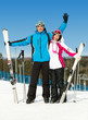 Full-length portrait of two hugging skiers with skis in hands