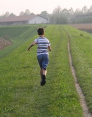 child runs along a country road