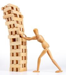 Wooden man figure pushing down tower