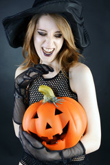 Frau in Kostüm Hexe zu Halloween mit Kürbis
