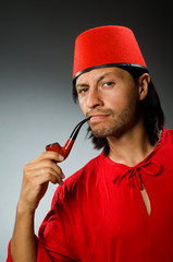 Man in red dress wearing fez hat