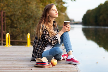 Young beautiful girl sitting on a pier
