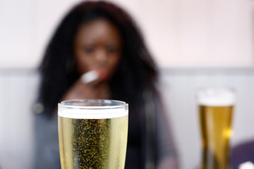 African woman drinking beer in a pub