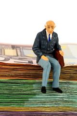 Senior sitzt auf Geldscheinen