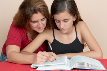 Hispanic teenage girl studying with her mother