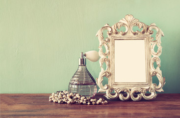 vintage antigue perfume bottles with old picture frame, on woode