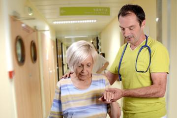 médecin aidant une vieille dame à marcher