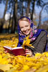 beautiful young girl lying on autumn leaves with red book