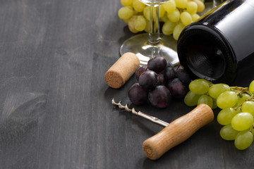 bottle of red wine and grapes on a wooden background