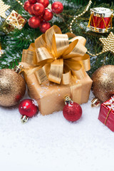 Golden gift box and Christmas tree decorations, vertical