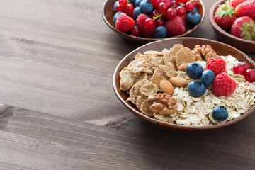 oatmeal, granola, nuts and berries on wooden background