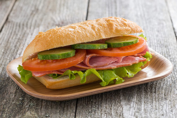 sandwich with ham and vegetables on wooden table, close-up