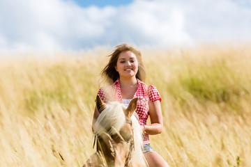 Frau reitet auf Pferd in Sommer Wiese
