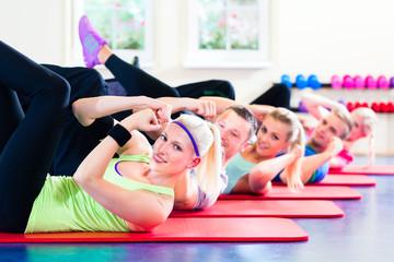 Fitness Gruppe im Studio bei Rumpfbeugen