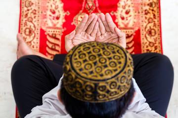 Asian Muslim man praying on carpet