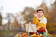 Cute little boy painting in golden autumn park