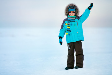 Cute little boy outdoors standing on winter sea
