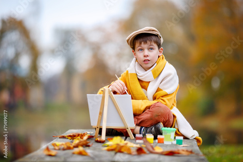 Leinwandbild Motiv Cute little boy painting in golden autumn park