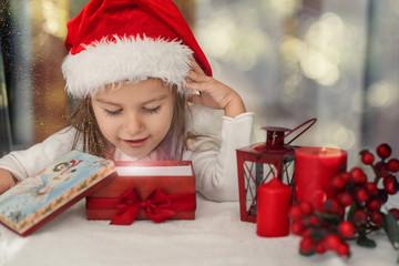 Little girl opening at present box. Magic shining gift