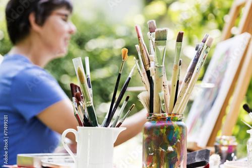 Leinwanddruck Bild Frau malt ein Bild im Garten