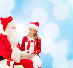 smiling little girl with santa claus and gifts