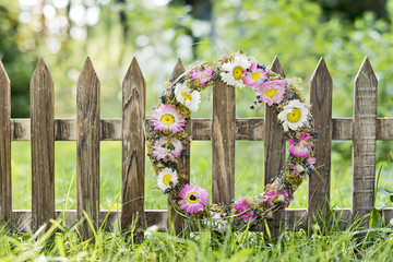 Blumenkranz hängt am Zaun