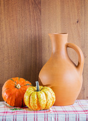 Jug and two pumpkins on the checkered napkin