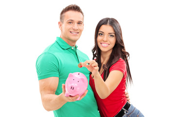 Young couple inserting money into a piggybank