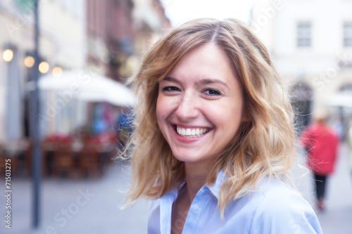 Leinwandbild Motiv Frau mit blonden Locken in der Stadt hat Spass