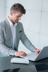 Stylish man sitting typing on a laptop