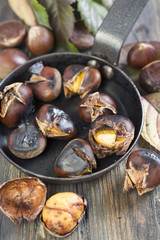 Frying pan with roasted chestnuts closeup.